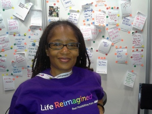 Ananda Leeke sitting behind the Life Reimagined comments of BlogHer attendees at AARP Expo Booth